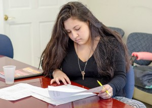 Devee-ana Douglas pulls out some homework during the new afterschool program at the Leominster Spanish American Center on Wednesday afternoon. SENTINEL & ENTERPRISE / Ashley Green